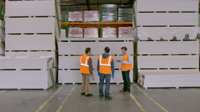 Three workers entering from behind camera, walk to stacked goods, after brief discussion turn and walk past camera to exit