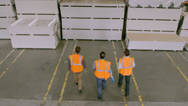 HA three workers entering warehouse and proceed to stacked goods, starting discussion