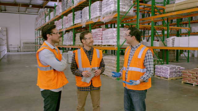 three workers having a meeting in a warehouse