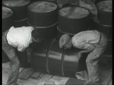 Three workers move heavy barrels on a ship
