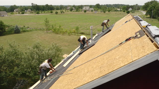 ms three workers removing and installing roof on red building / chelsea, michigan, united states - provincial reconstruction team stock videos & royalty-free footage