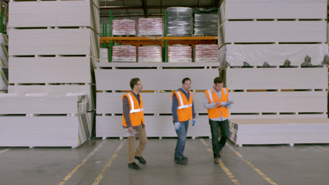 Three workers standing in front of stacked goods in warehouse, having a discussion; turn to camera and exit frame passing camera