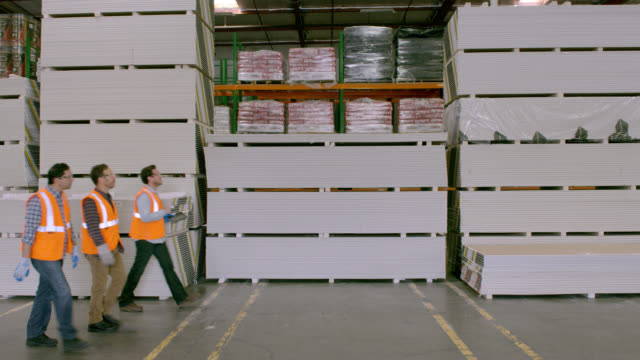 three workers walking along stacks of goods in warehouse, left to right; camera is locked off