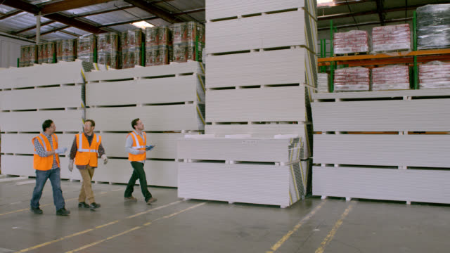 PAN three workers walking along stacks of goods in warehouse, left to right