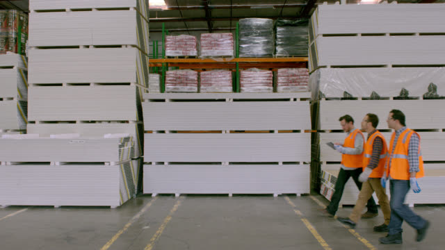 three workers walking along stacks of goods in warehouse, right to left; camera is locked off