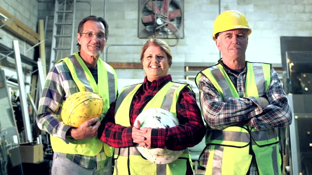 three workers with hardhats and safety vest - tecnico video stock e b–roll