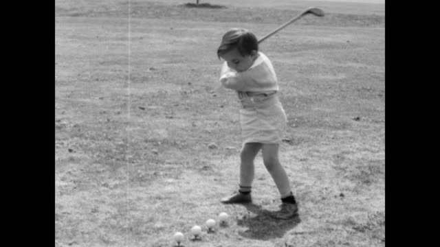 / three year old Edward T Rule is blindfolded on the golf course to perform his trick shot / toddler hits ball off man's hands and shoes / toddler...