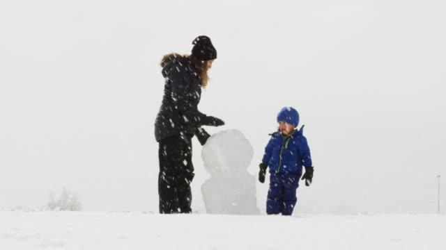 drei jahre alten kaukasischen jungen und seine kaukasischen mutter in ihren dreißigern (beide in winterkleidung gekleidet) machen einen schneemann zusammen an einem verschneiten, bedecktem tag - schneemann stock-videos und b-roll-filmmaterial