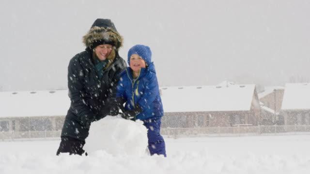 3 歳の白人少年と 30 代の彼の白人の母親 (冬の服を着ての両方) は雪で雪だるまを一緒に作る、曇りの日 - ウィンターコート点の映像素材/bロール