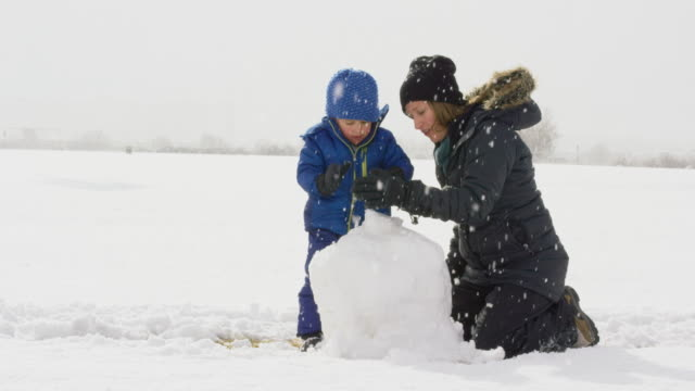 three year-old caucasian boy and his caucasian mother in her thirties (both dressed in winter clothing) make a snowman together on a snowy, overcast day - snowman stock videos & royalty-free footage