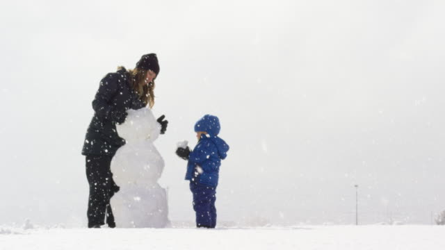 three year-old caucasian boy and his caucasian mother in her thirties (both dressed in winter clothing) make a snowman together on a snowy, overcast day - making a snowman stock videos & royalty-free footage
