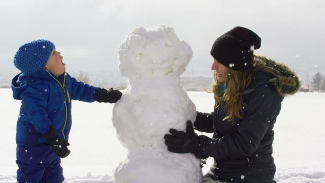 three year-old caucasian boy and his thirty-something mother (both dressed in winter clothing) put stick arms on a snowman on a snowy day - making a snowman stock videos & royalty-free footage