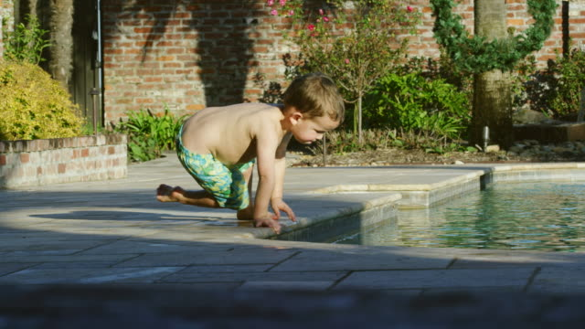 a three year-old caucasian boy crawls to the edge of a swimming pool and puts his hand in the water on a sunny summer day - safety stock videos & royalty-free footage