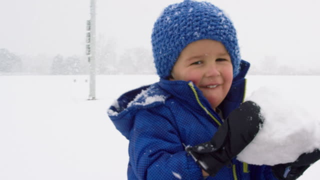three year-old caucasian boy dressed in winter clothing rolls a snowball on the ground and picks it up on a snowy, overcast day - snowman stock videos & royalty-free footage