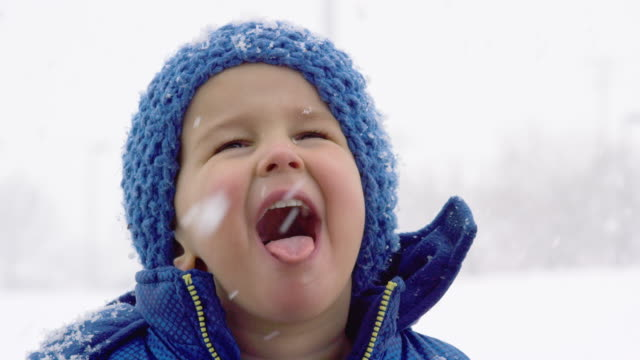 three year-old caucasian boy dressed in winter clothing tries to catch snowflakes on his tongue on an overcast day - toddler stock videos & royalty-free footage