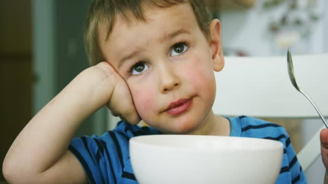 vídeos de stock, filmes e b-roll de um menino caucasiano dos anos de idade três come a massa do macarrão e do queijo de uma bacia com uma colher em uma tabela da cozinha dentro ao sorrir - 2 3 anos