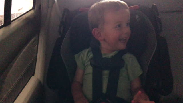 vidéos et rushes de un garçon caucasien de trois ans regarde autour de lui avec enthousiasme dans son siège-auto comme il roule sur la route - excitation