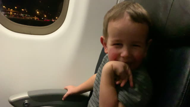 a three year-old caucasian boy looks out the window of a commercial airliner jet passenger plane and laughs at the camera while a five year-old caucasian boy and his thirty-something caucasian mother also enjoy taking off on an airplane at night - anticipation stock videos & royalty-free footage