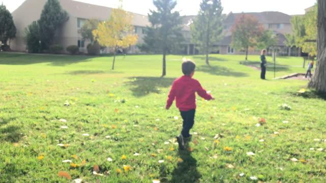 vidéos et rushes de un garçon de trois ans caucasien traverse une pelouse herbeuse pour rejoindre son frère et sa mère sur un petit terrain de jeu dans un parc de quartier à l'automne sur une journée ensoleillée - famille avec enfants