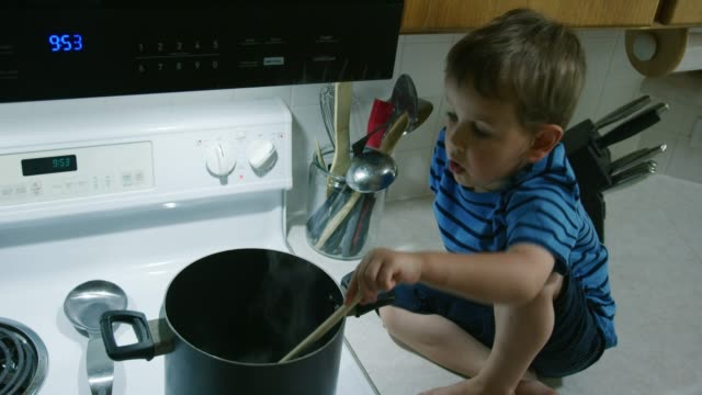 A Three Year-Old Caucasian Boy Sits on the Counter in the Kitchen and Stirs Liquid in a Large Pot that is Sitting on a Stove Top Range