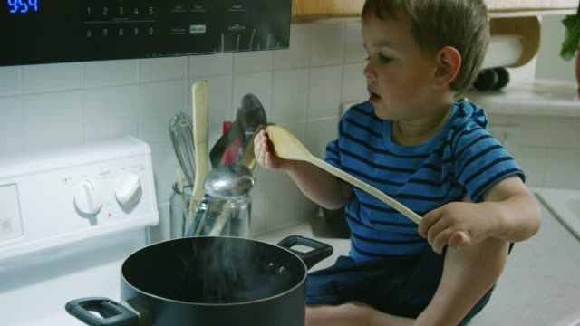 a three year-old caucasian boy sitting on the counter in the kitchen pulls a wooden spoon out of a pot of hot water on the stove top range and recoils after he feel it is hot - innocenza video stock e b–roll