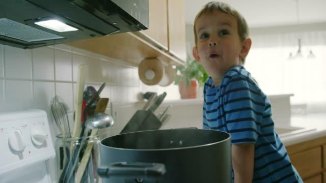 3歳の白人の男の子が台所でストーブのトップレンジに座っている蒸し鍋を見ながら話す - ストーブ点の映像素材/bロール