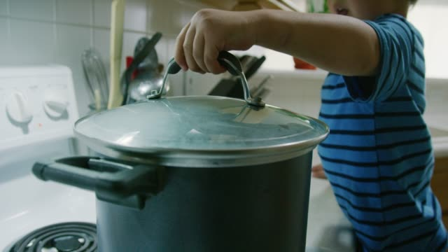 a three year-old caucasian boy talks while placing a glass lid on to a steaming pot that is sitting on a stove top range in a kitchen - cooking pan stock videos & royalty-free footage