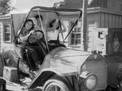 stockvideo's en b-roll-footage met three young adult females sitting in front seat of early 20th century car pretending to honk horn laughing smiling jalopy classic vintage antique car... - 1952
