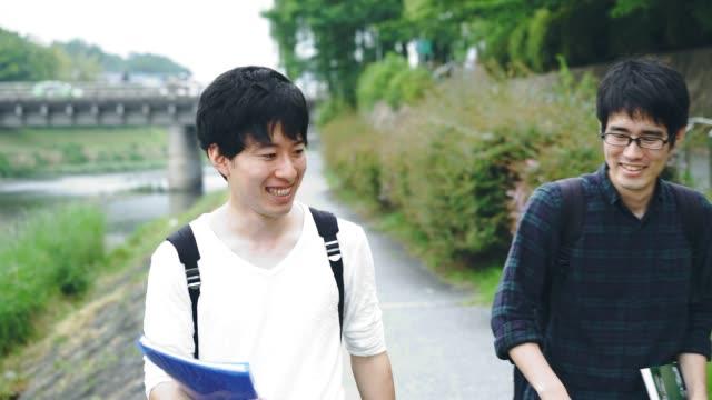 一緒に歩いて 3 つの若い大人の学生 - 歯を見せて笑う点の映像素材/bロール