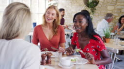 Three young adult women having brunch together and talking in a small restaurant, waist up