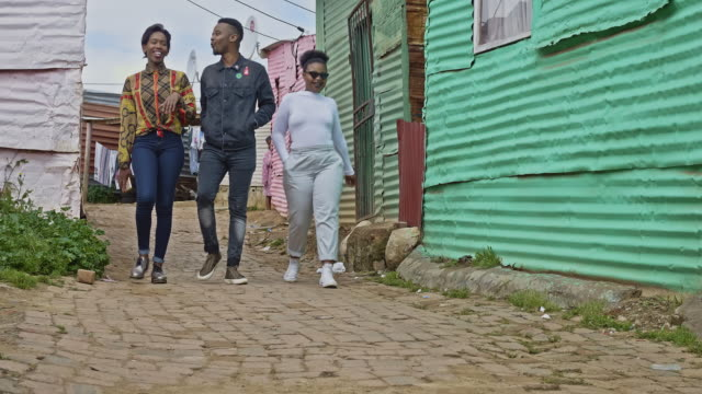 three young african friends walking in a township street in cape town - south africa stock videos & royalty-free footage