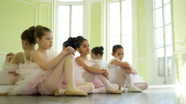 vídeos de stock e filmes b-roll de three young ballerinas lean against the studio mirror taking a break from their training - body de ginástica