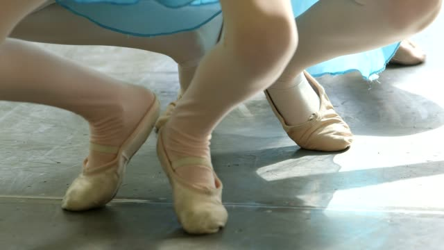 Three young Ballerinas stretch and extend in a row using the Ballet barre