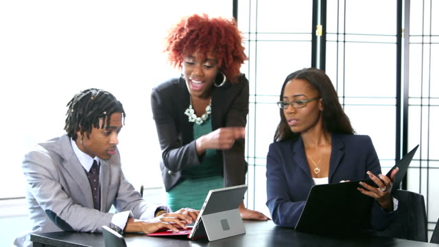 Three young black business people working together