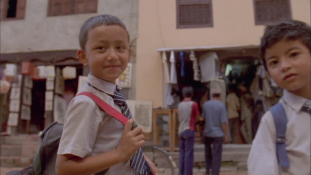 three young boys in school uniform, one with broken arm, smile and wave at camera, baktapur available in hd. - braccio umano video stock e b–roll
