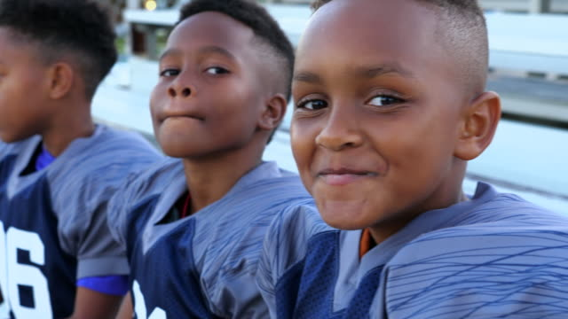 PAN Three young boys sitting together on bleachers after football practice