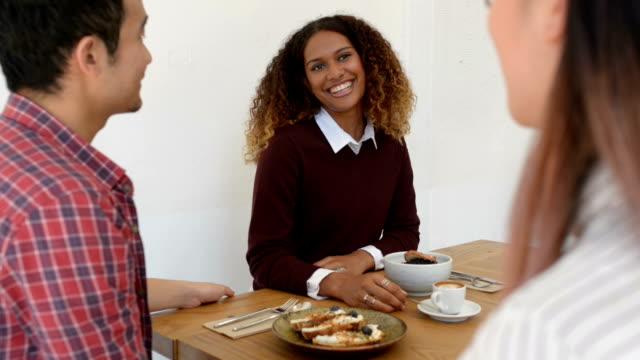 vídeos de stock e filmes b-roll de three young business people in discussion at cafe - pão de fermento