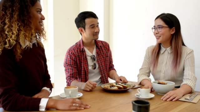 Three Young Business People in Discussion at Cafe