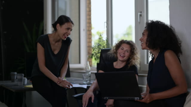 Three young businesswomen looking at laptop, having conversation