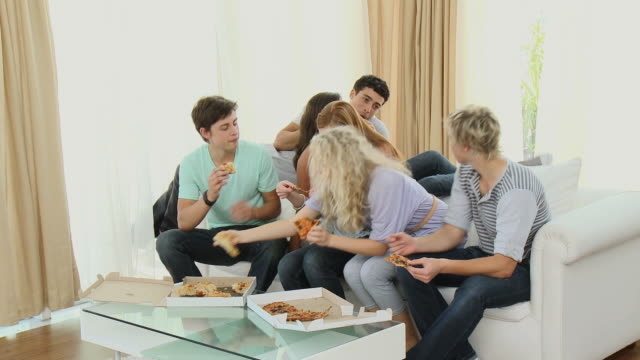 MS Three young couples (girl 14-15) eating pizza in living-room on sofa / Cape Town, South Africa