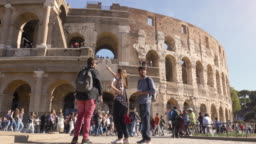 Three young friends tourists standing in front of colosseum in rome reading map guide for directions pointing with backpacks sunglasses happy beautiful girl long hair