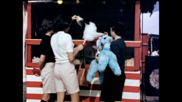 three young girls one holding a stuffed animal in front of a food stand / girls eat cotton candy off sticks as they turn to leave / candy maker... - kuchen und süßwaren stock-videos und b-roll-filmmaterial