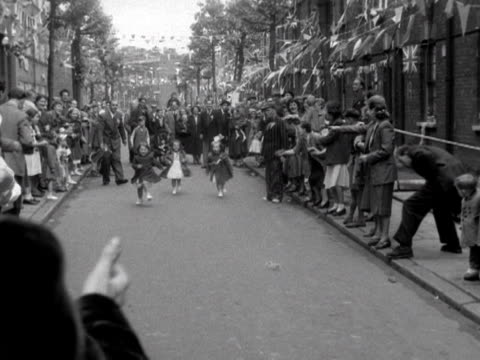 three young girls take part in a race during a street party for the coronation 1953 - 1953 stock videos and b-roll footage