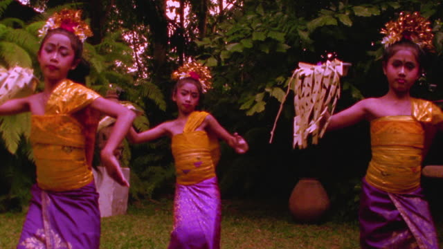 ms three young indonesian girls performing traditional dance in native dress outdoors / bali - balinese culture stock videos & royalty-free footage
