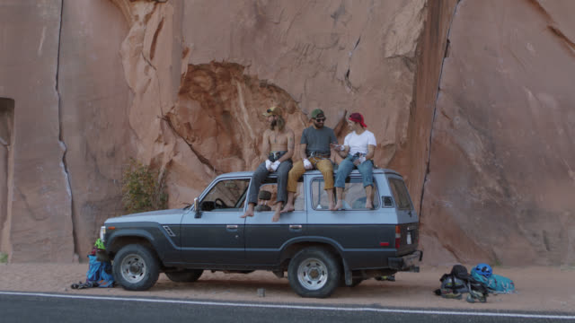 slo mo. three young men chat and inspect hand tape on the roof of vehicle at the base of sandstone rock face on moab climbing trip. - rock face stock videos & royalty-free footage
