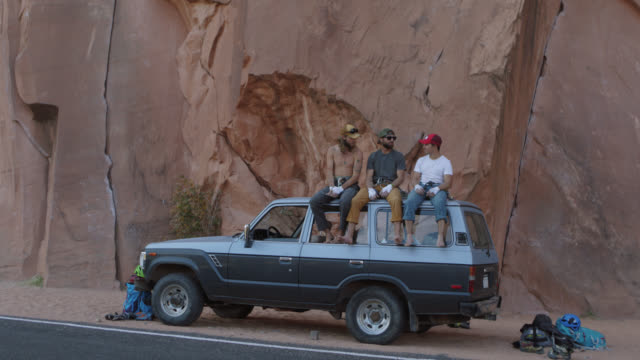 SLO MO. Three young men fist bump and talk on the roof of vehicle at the base of sandstone rock face on Moab climbing trip.