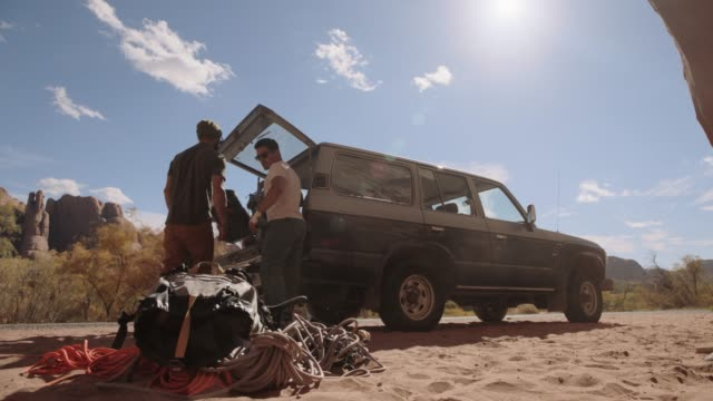 vídeos de stock, filmes e b-roll de three young men get out of vehicle and unload climbing gear in the sand on scenic utah roadside. - terreno extremo