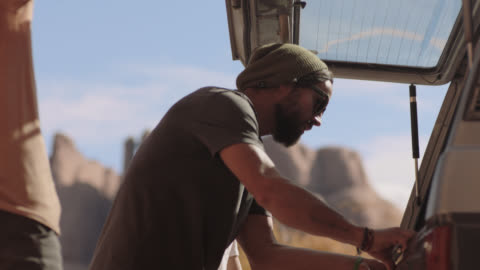 vidéos et rushes de three young men lift rear hatch and unload rope and climbing gear from vehicle on scenic utah roadside. - décharger