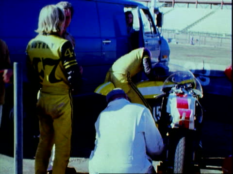 vídeos de stock e filmes b-roll de three young men with very long greasy hair tshirts and black riding leathers while talking beside road bike motorcycle at riverside international... - hippie
