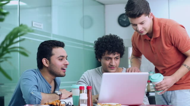 Three young men working on a laptop in the cafeteria